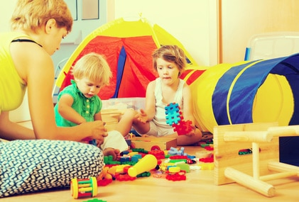 2 young children with play tent and construction toys