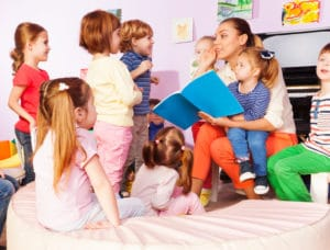 Preschool Teacher with kids boys and girls read and discuss book sitting together in the class